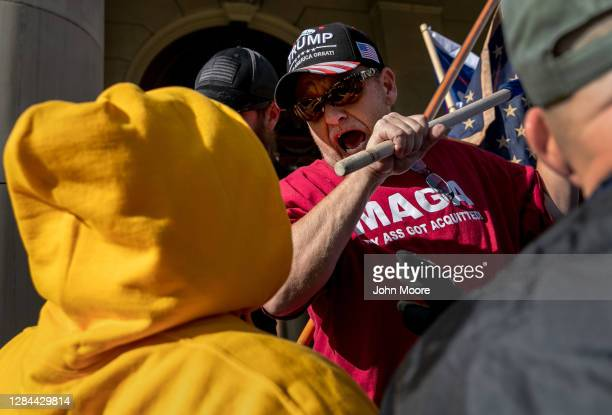 Trump supporter threatens a counter-protester during a demonstration over election ballot counting outside the Michigan State Capitol building on...
