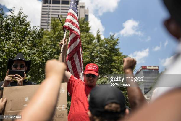 Trump supporter waves a flag during an 'Anti-Mask' rally at Ohio Statehouse. Over 200 people gathered at the Ohio State House to protest against the...