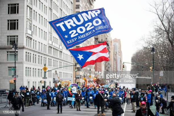 Trump supporter waves a huge flag with TRUMP 2020 Keep America Great! walks in front of the marchers as they start the march on Central Park West...