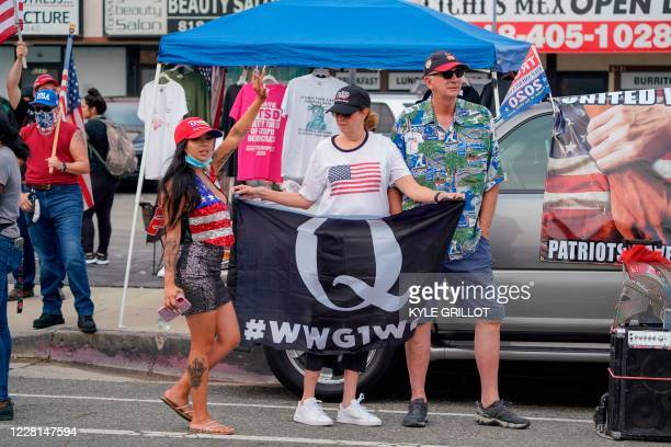 Trump supporter waves a Qanon flag towards passing cars and counter-protestors standing across the road in Tujunga, a north neighborhood of Los...