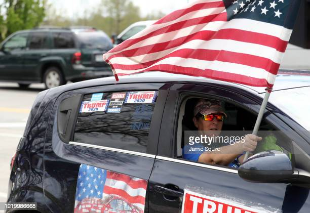 Trump supporter waves an American flag during a protest encouraging people to demand that businesses be allowed to open up, and people go back to...