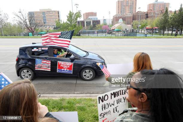 Trump supporter waves an American flag during a protest encouraging people to demand that businesses be allowed to open up, and people allowed to go...
