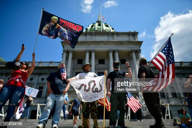 Trump supporters and a man with an assault rifle join demonstrators outside the Pennsylvania Capitol Building to protest the continued closure of...