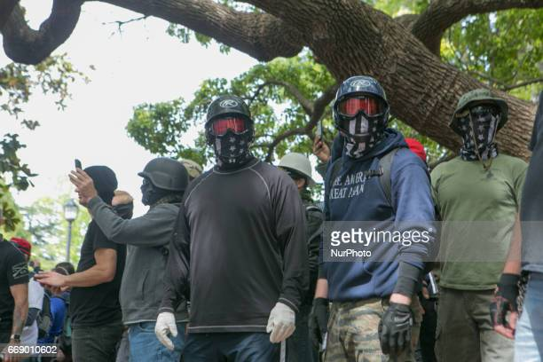 Trump supporters cover their faces in anticipation for fighting during a free speech rally at Martin Luther King Jr Civic Center Park in Berkeley...