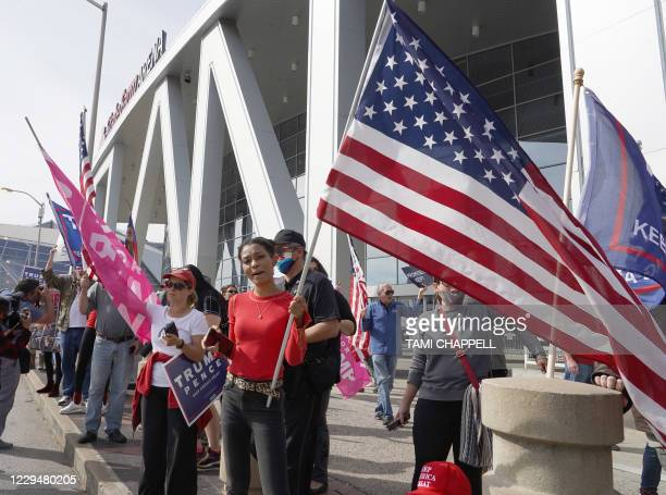 Trump supporters hold signs and flags during a protest outside State Farm Arena where Fulton County Elections officials aree counting ballots,...