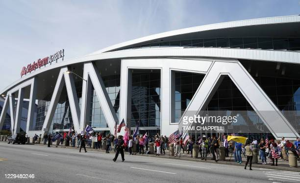 Trump supporters hold signs during a protest outside State Farm Arena where Fulton County Elections officials aree counting ballots, November 5 in...