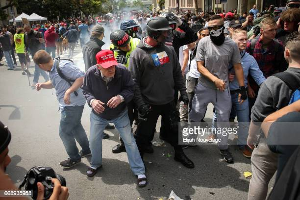 Trump supporters react to a flash bang grenade during a clash with protesters at a 'Patriots Day' free speech rally on April 15 2017 in Berkeley...