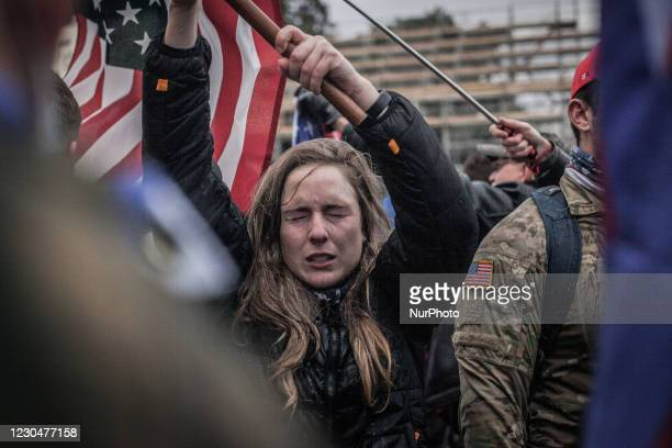 Trump supporters waves an american flag as their eyes sting near the U.S. Capitol on January 06, 2021 in Washington, DC. The protesters stormed the...