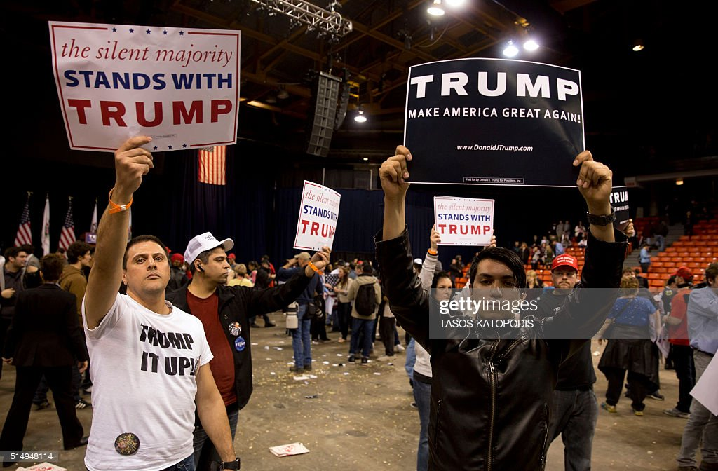 Trump suppoters hold campaign signs during a Trump rally at the UIC Pavilion in Chicago on March 11, 2016. Republican White House hopeful Donald Trump cancelled his appearance at a Chicago rally Friday amid extraordinary scenes of chaos, with hundreds of protesters clashing with the frontrunner's supporters and police struggling to maintain order. / AFP / Tasos KATOPODIS