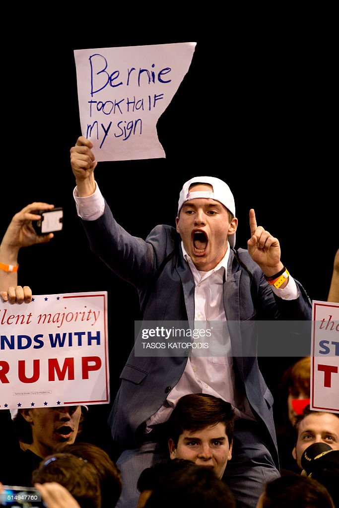 Trump suppoters shout to anti-Trump protesters during a Trump rally at the UIC Pavilion in Chicago on March 11, 2016. Republican White House hopeful Donald Trump cancelled his appearance at a Chicago rally Friday amid extraordinary scenes of chaos, with hundreds of protesters clashing with the frontrunner's supporters and police struggling to maintain order. / AFP / Tasos KATOPODIS