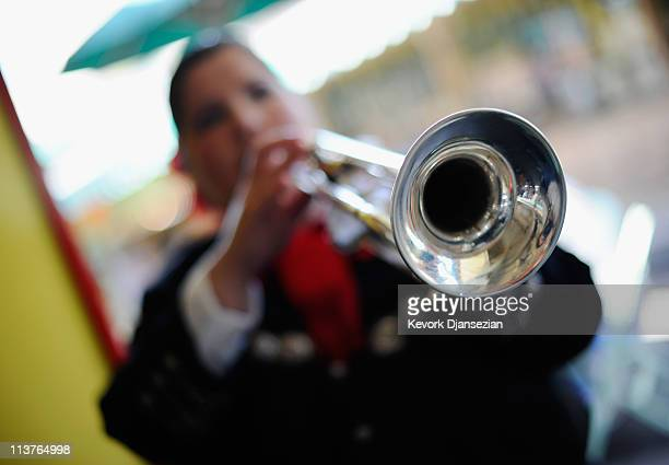 Trumpet player Esmeralda Garcia a member of the allfemale strolling Mariachi band Ellas Son performs at Los Angeles Farmer Market during Cinco de...