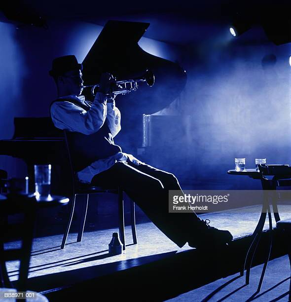 trumpet player performing in empty club (toned b&w) - blues music stock pictures, royalty-free photos & images