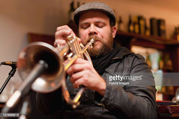 Trumpet player playing into microphone