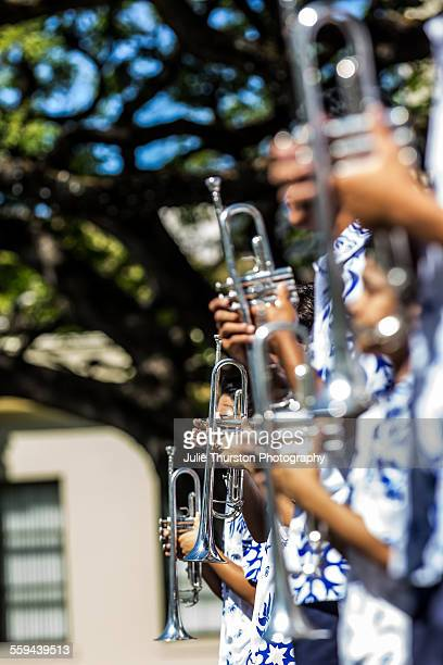 Trumpet players in aloha shirts from the Hawaiian Kamehameha School marching band marching and playing in the annual local downtown King Kamehameha...