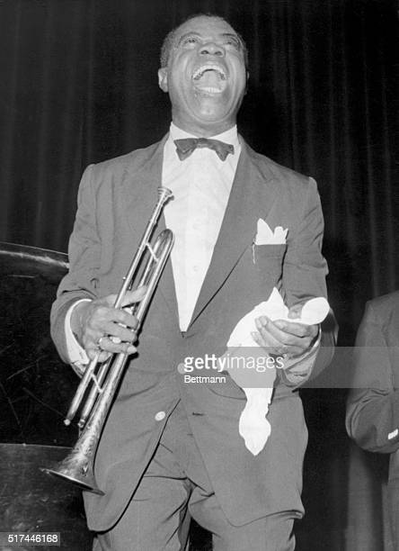 Trumpeter Louis Armstrong holds his trumpet and a spit rag as he smiles on stage.
