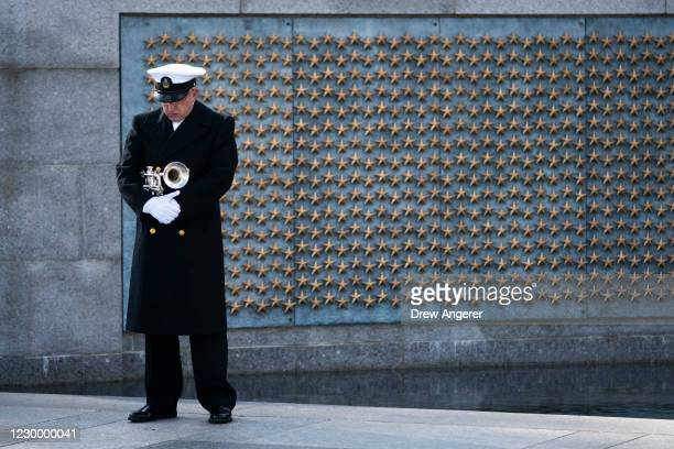 Trumpeter with a military honor guard pauses at the World War II Memorial during a wreath-laying ceremony to mark National Pearl Harbor Remembrance...