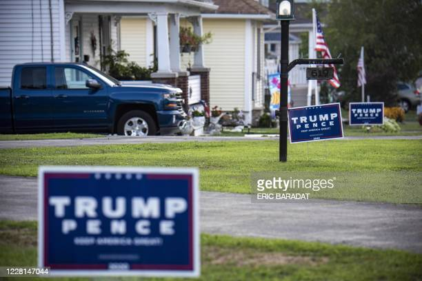 TrumpPence signs and banners are seen on a street in Olyphant just outside Scranton Pennsylvania on August 11 2020 It is not hard to miss the border...