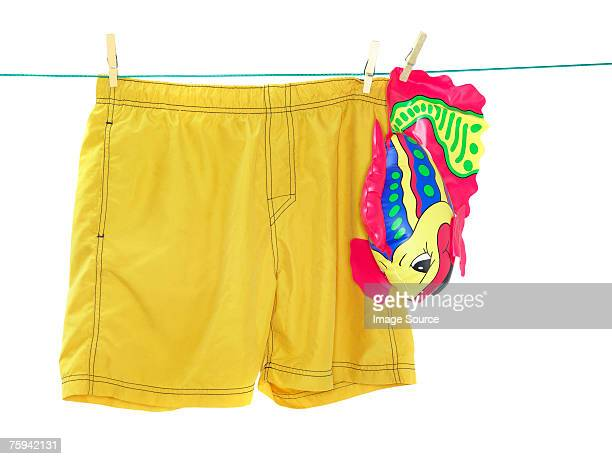 trunks and an inflatable toy on a washing line - calzoncini da bagno foto e immagini stock