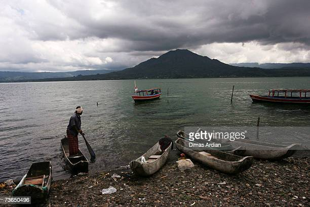 Trunyan villager travels on a traditional boat with Mount Batur and Lake Batur behind near a village cemetery in Kuban on March 21 2007 near Trunyan...