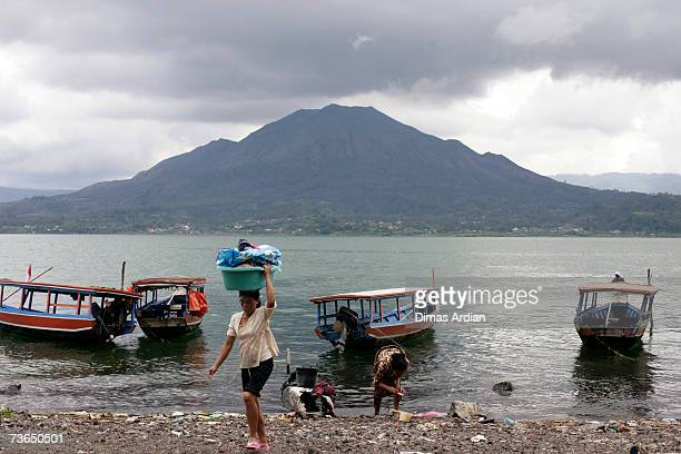 Trunyan villagers wash their clothes in Lake Batur with Mount Batur behind near a village cemetery in Kuban on March 21 2007 near Trunyan Bali resort...