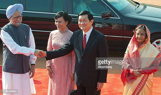 Truong Tan Sang Vietnam's president second right shakes hands with Manmohan Singh India's prime minister left as Sang's wife Mai Thi Hanh second left...