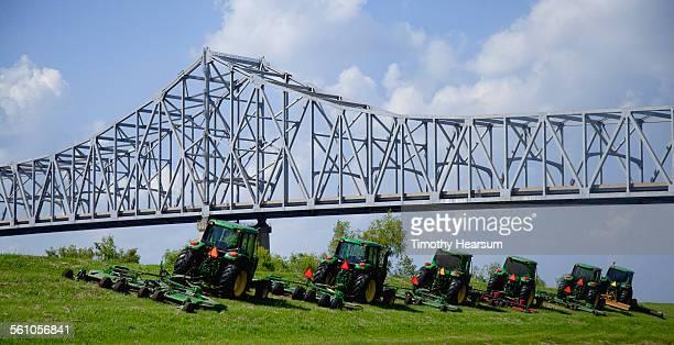 truss bridge, row of large mowers on river dike - timothy hearsum stock-fotos und bilder