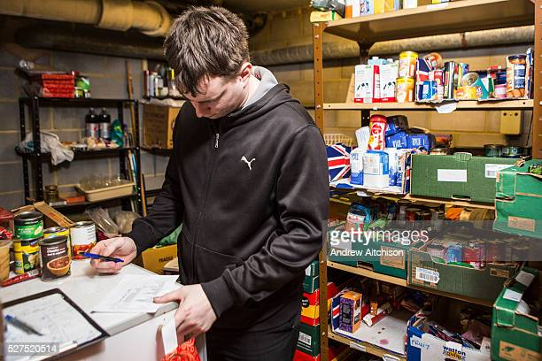 A Trussell Trust foodbank volunteer uses a checklist form to prepare an emergency food box for a family who are unable to provide enough food for...