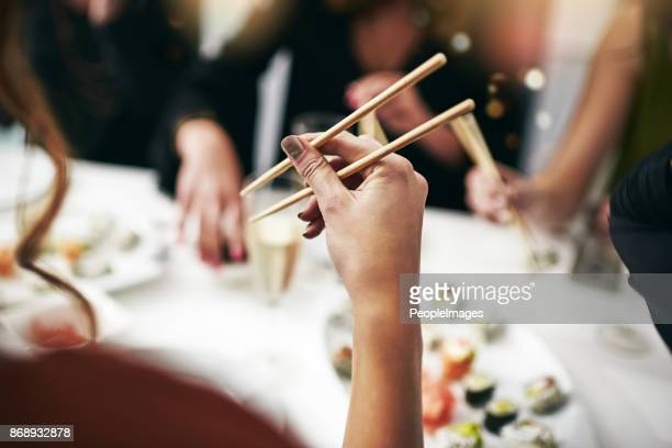 trying her hand at using the chopsticks - sushi stock pictures, royalty-free photos & images