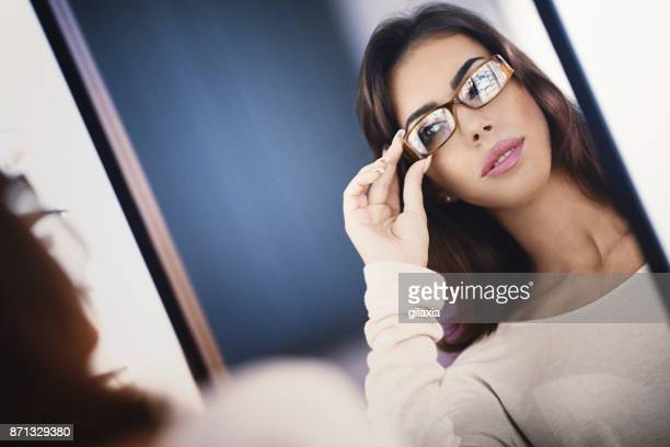 Trying on a new pair of eyeglasses in front of a mirror.