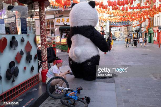 Trying to earn some money from tourists dressed up as a Giant Panda on the corner of Gerrard Street in Chinatown which remains very quiet with a few...