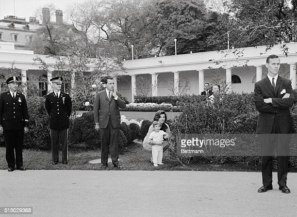 Trying to stay in the background Mrs Jacqueline Kennedy and her son John Jr peep out from behind shrubbery as they watch ceremonies on the south...