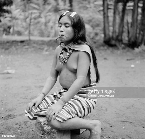 Tsachila tribal girl in the traditional red facial markings and striped clothes poses as she smokes in Domingo de los Colorados Ecuador