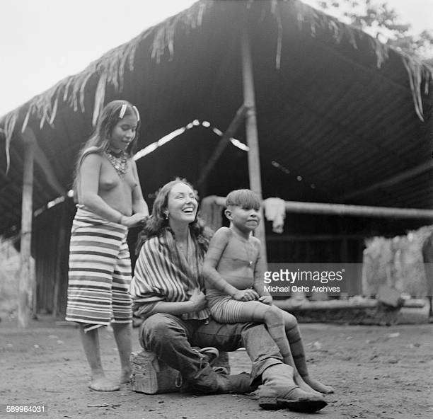 Tsachila tribal woman helps to decorate a visiting woman in the traditional red facial markings and striped clothes in Domingo de los Colorados...