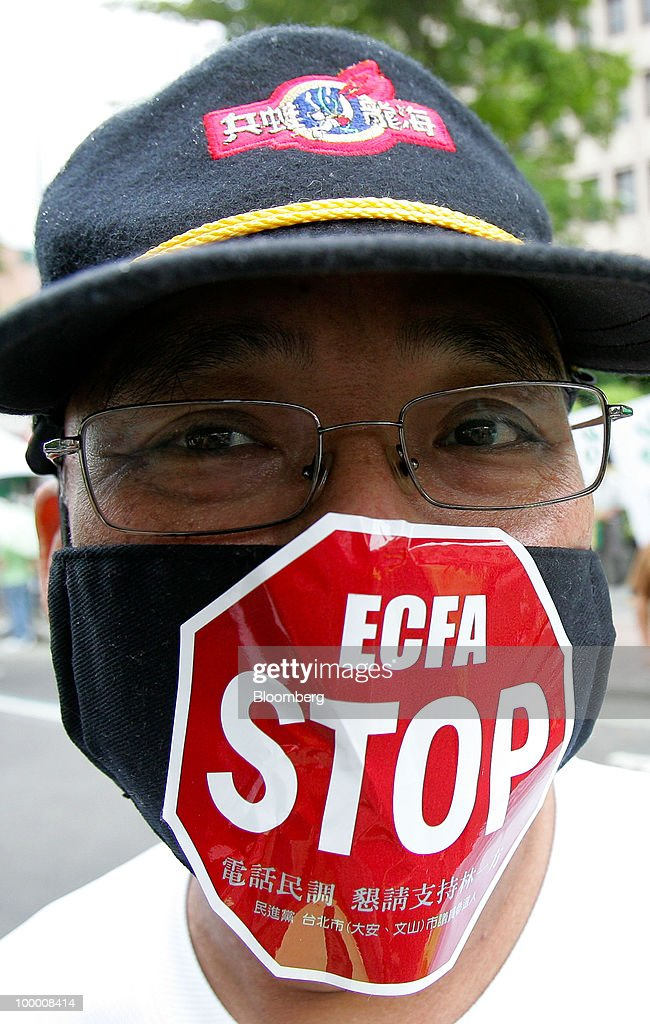 K. K. Tseng, a supporter of opposition Democratic Progressive Party (DPP), wears a mask at a sit-in protest in Taipei, Taiwan, on Thursday, May 20, 2010. President Ma Ying-jeou has pushed for the trade agreement with China to prevent Taiwan from being 'marginalized' after a Chinese accord with the 10-member Association of Southeast Asian Nations took effect this year. The proposal sparked opposition demonstrations amid concern China may boost its influence over Taiwan. Photographer: Maurice Tsai/Bloomberg via Getty Images