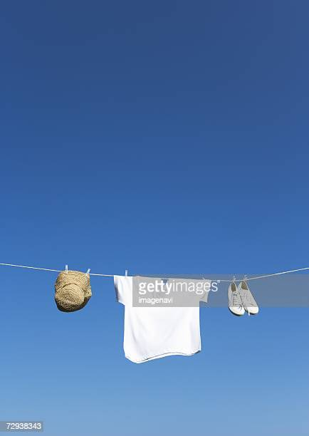 T-shirt,  hat and shoes hanging on clothesline