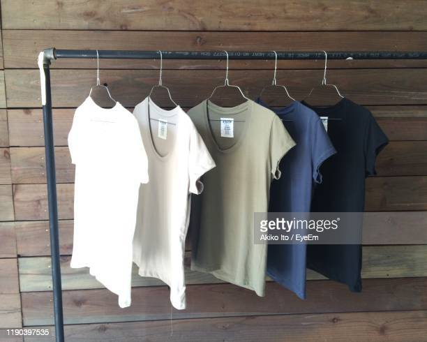 t-shirts hanging against wooden wall - 収納ラック ストックフォトと画像