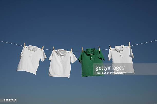 t-shirts on a washing line against a blue sky. - 洗濯物 ストックフォトと画像