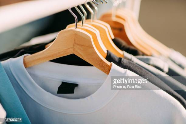t-shirts on hangers - t shirt stock pictures, royalty-free photos & images
