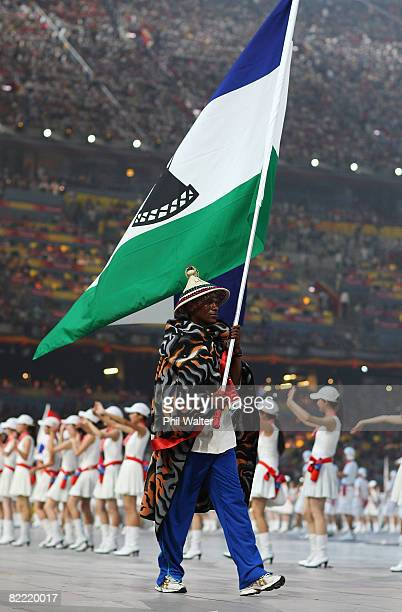 Tsotang Maine of the Lesotho Olympic track and field team carries his country's flag to lead out the delegation during the Opening Ceremony for the...