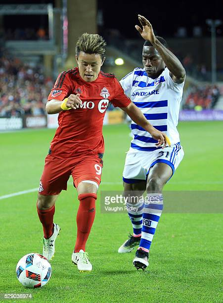 Tsubasa Endoh of Toronto FC battles for the ball with Maynor Figueroa of FC Dallas during the second half of an MLS soccer game at BMO Field on May 7...