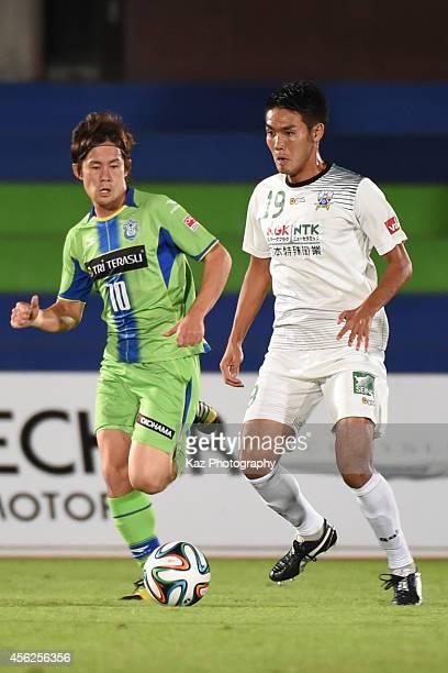 Tsukasa Masuyama of FC Gifu keeps the ball while Daisuke Kikuchi watches during the J. League second division match between FC Gifu and Shonan...