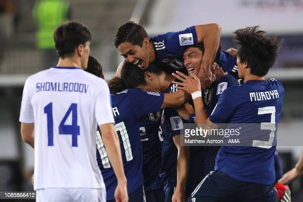 Tsukasa Shiotani of Japan celebrates scoring a goal to make it 2-1 with his team-mates during the AFC Asian Cup Group F match between Japan and...