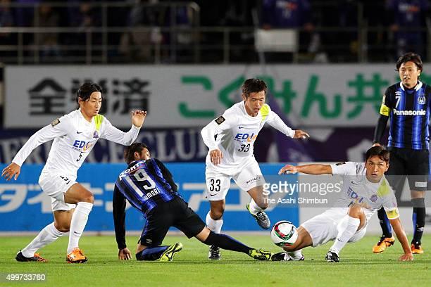 Tsukasa Shiotani of Sanfrecce Hiroshima and Kotaro Omori of Gamba Osaka compete for the ball during the JLeague Championship Final frist leg match...