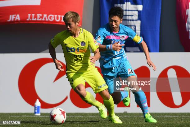 Tsukasa Shiotani of Sanfrecce Hiroshima and Yohei Toyoda of Sagan Tosu compete for the ball during the JLeague J1 match between Sagan Tosu and...