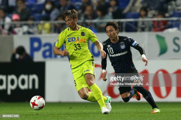 Tsukasa Shiotani of Sanfrecce Hiroshima controls the ball under pressure of Shu Kurata of Gamba Osaka during the JLeague J1 match between Gamba Osaka...