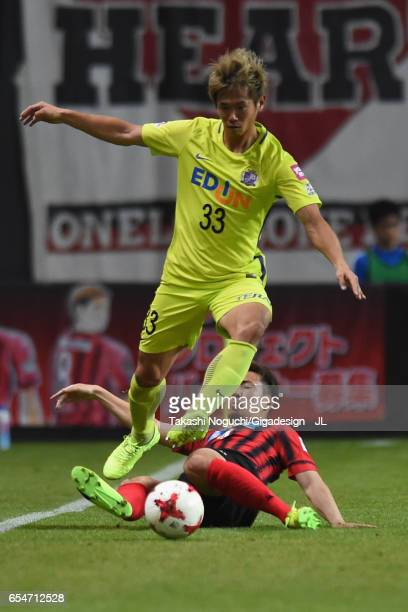 Tsukasa Shiotani of Sanfrecce Hiroshima is tackled by Shinya Uehara of Consadole Sapporo during the JLeague J1 match between Consadole Sapporo and...