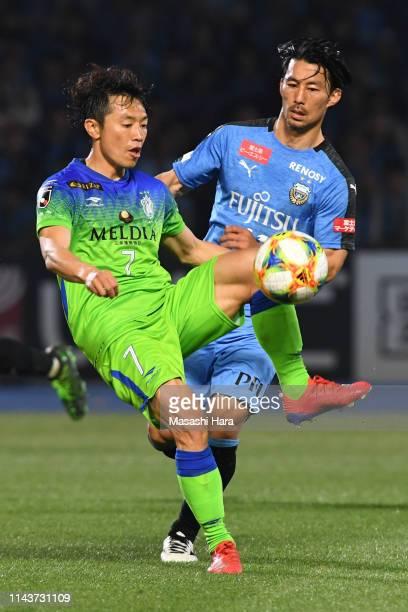 Tsukasa Umesaki of Shonan Bellmare and Akihiro Ienaga of Kawasaki Frontale compete for the ball during the J.League J1 match between Kawasaki...