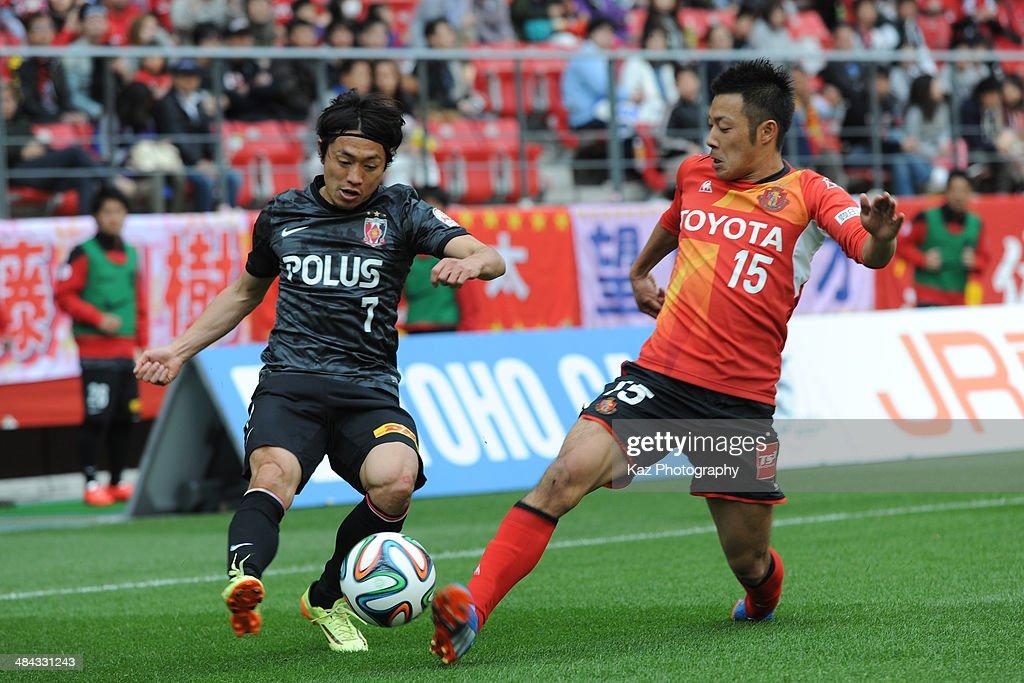 Tsukasa Umesaki (L) of Urawa Red Diamonds and Yuki Honda of Nagoya Grampus compete for the ball during the J. League match between Nagoya Grampus and Urawa Red Diamonds at the Toyota Stadium on April 12, 2014 in Toyota, Japan.