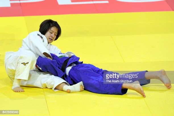 Tsukasa Yoshida of Japan holds Helene Receveaux of France to win in the Women's 57kg semi final during day three of the World Judo Championships at...