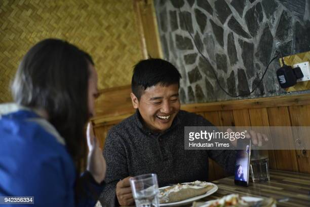 Tsultrim who is from Tibet and his partner Mauli speak to his mother who stays in Tibet on WeChat an application to communicate while having lunch at...